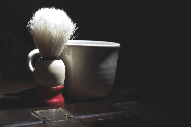 Shaving brush with shaving mug in dark area