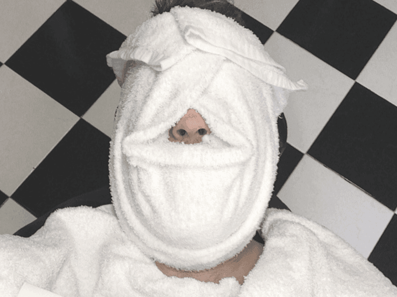 Man with hot towel on face
