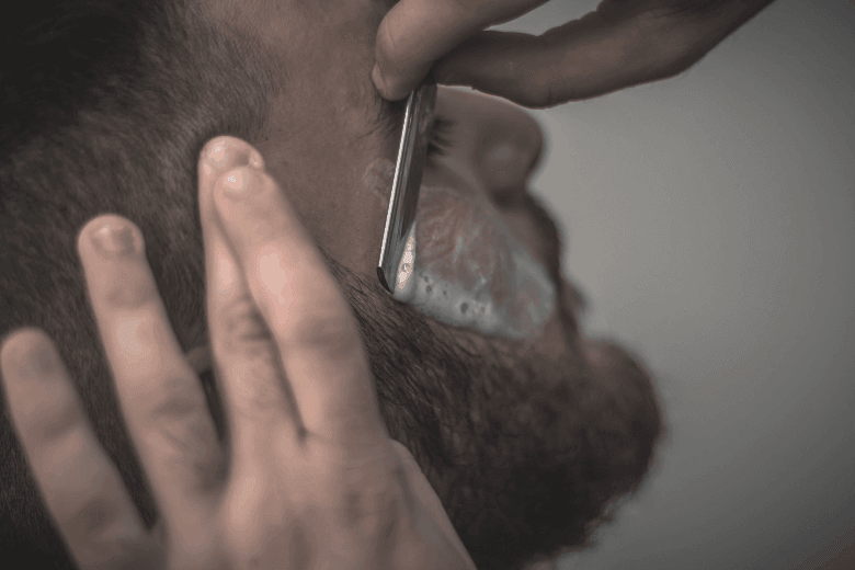 Man receiving a shave on the cheek