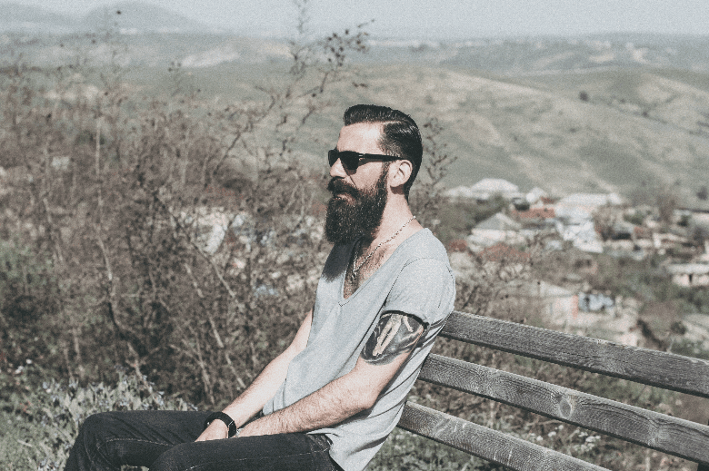 man with beard sitting on bench in the hills