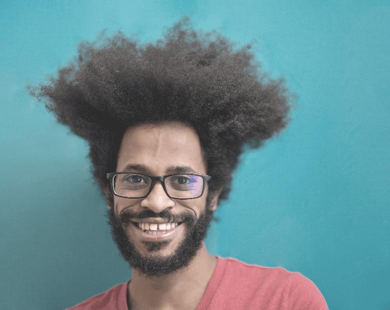 man with puffy hair smiling at camera