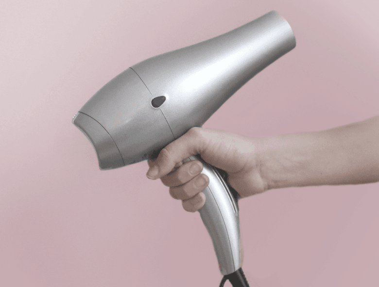 hand holding a silver hair dryer on a pink background
