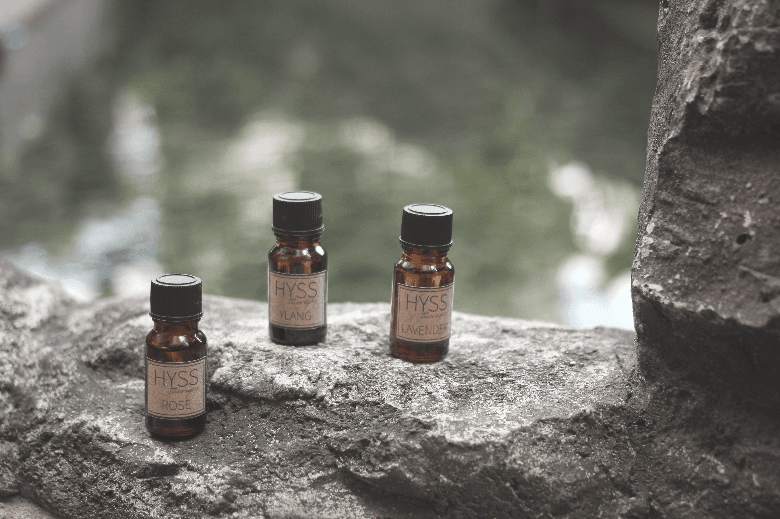 Three bottles of essential oils on a rock