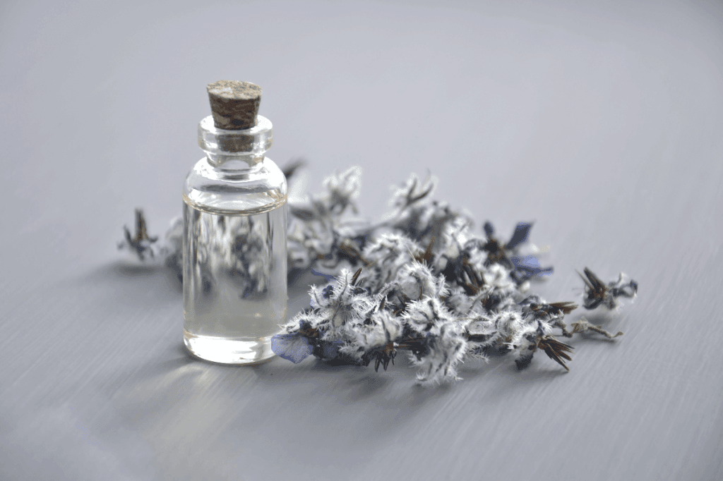 Bottle with cork next to purple flowers