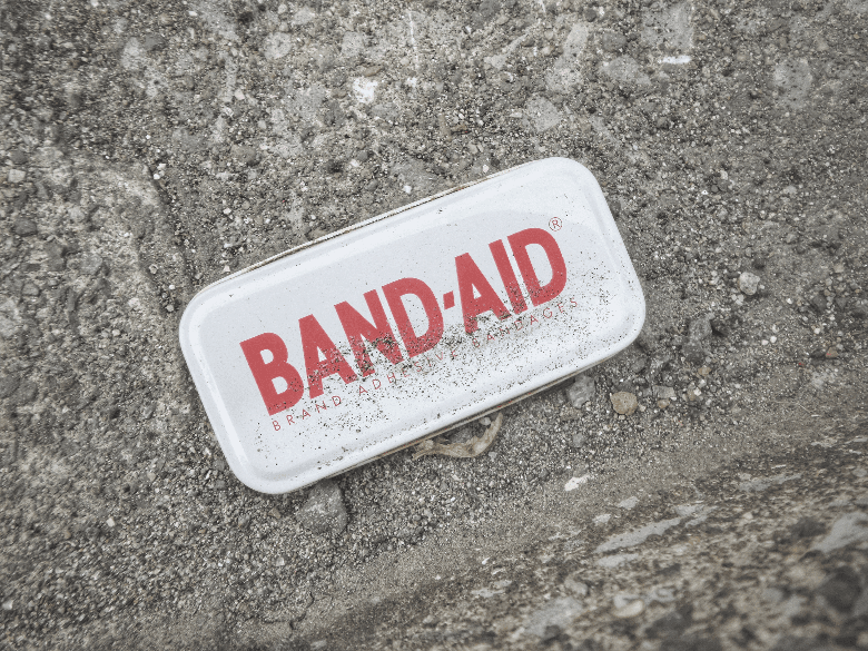 metal band-aid box on dirt