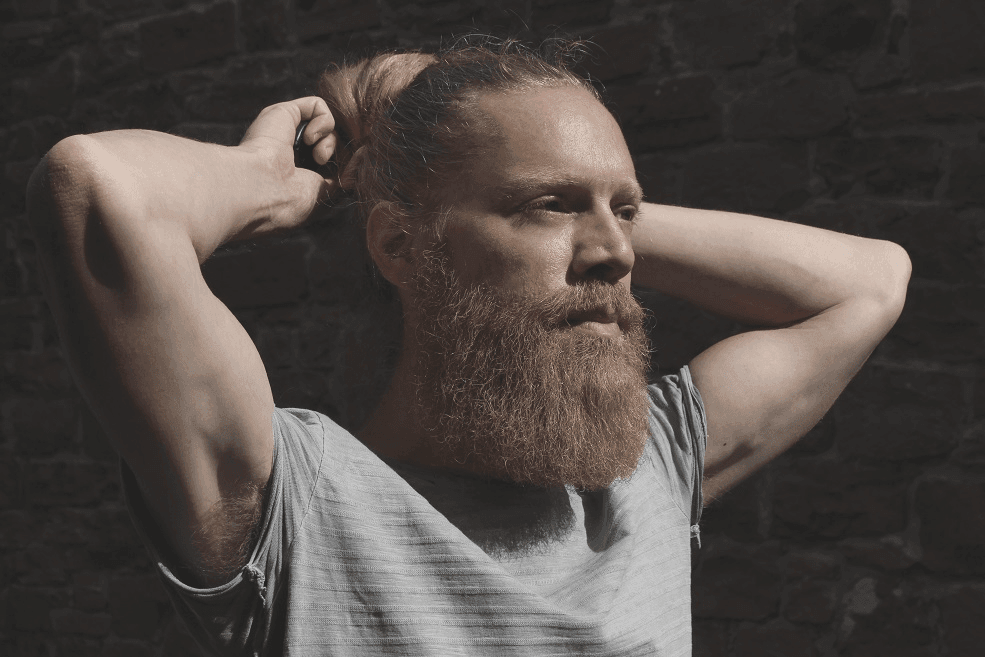 Man with beard adjusting long hair