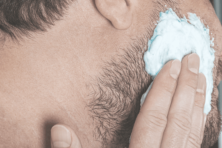 Applying shaving cream to beard