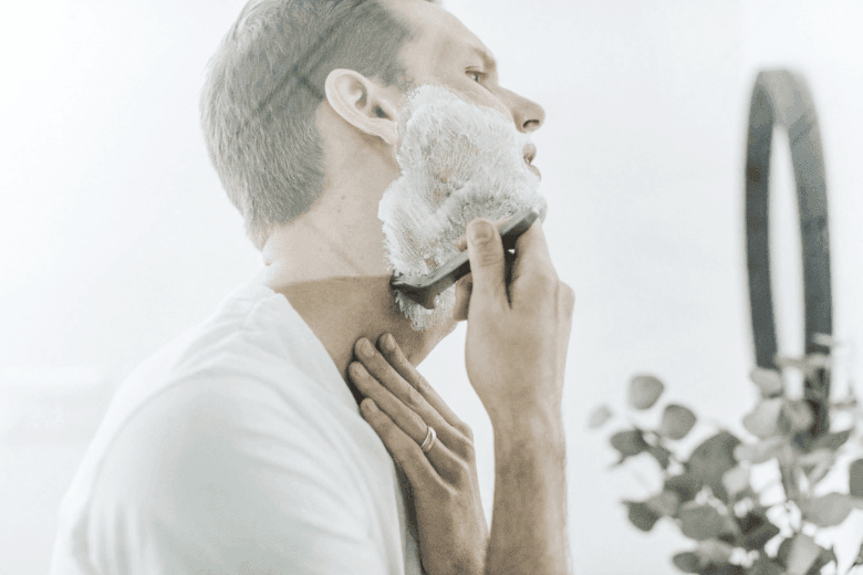 Man shaving neck in front of a bathroom mirror
