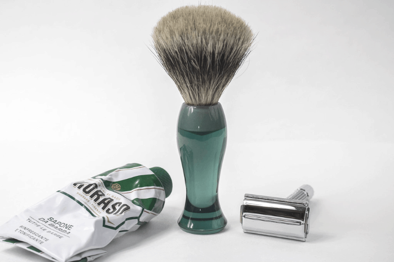 Double edge razor next to a shaving brush and shaving cream