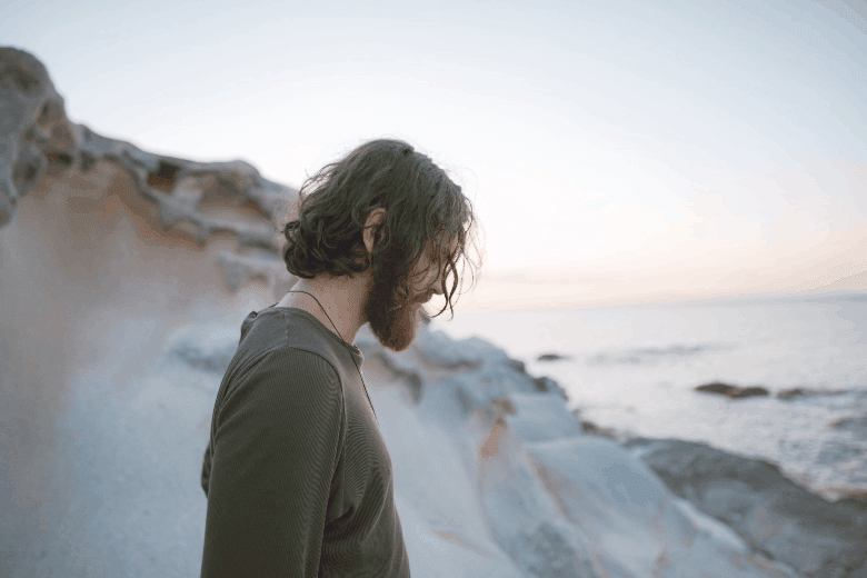 Man on beach in green sweatshirt with long hair and beard looking down on the ground
