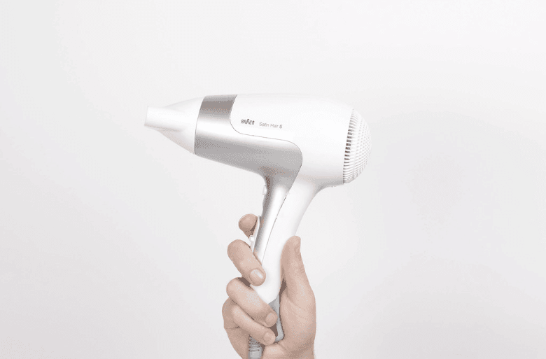 Blow dryer being held up by one hand