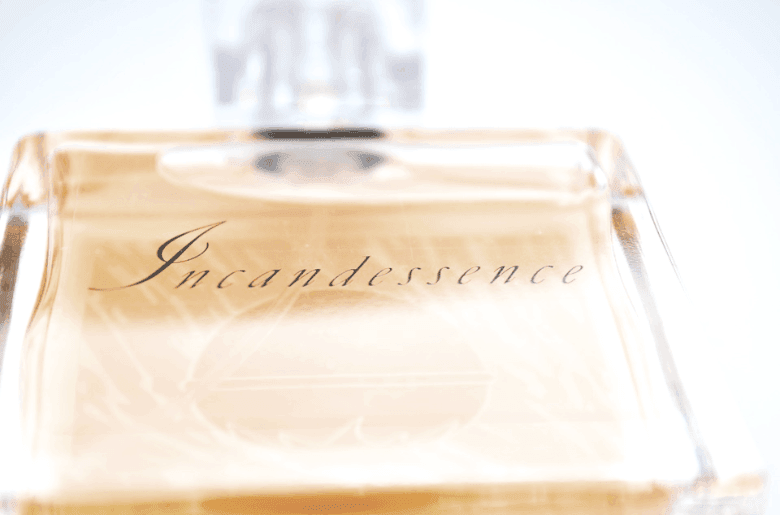 Bottle of golden perfume on white background