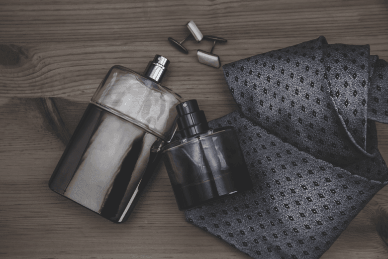 Perfume with tie and cufflinks on wooden table