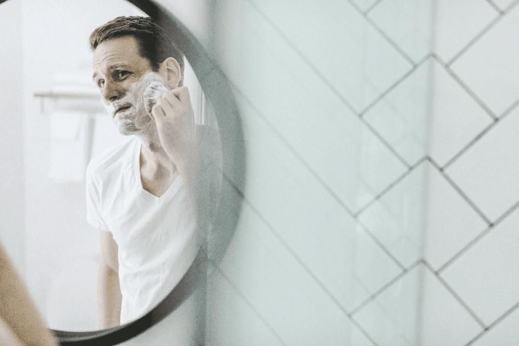 Man in mirror applying shaving cream