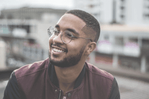 Man with glasses smiling against blurred background