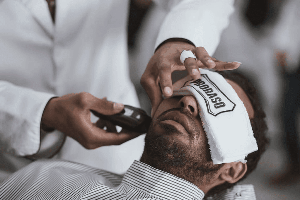 man receiving a trim on cheek with hot towel over eyes