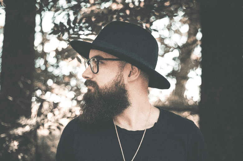 Man in woods with a black hat and black beard