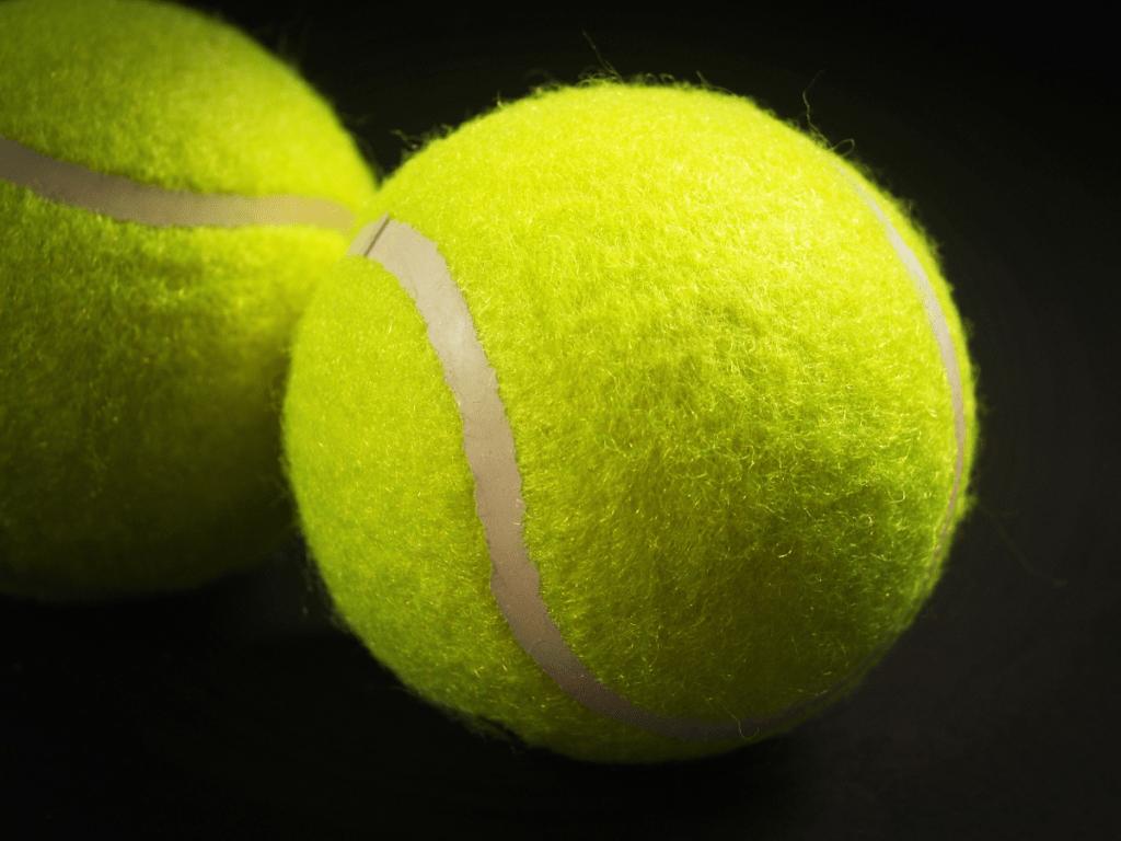 Two tennis balls on a dark background