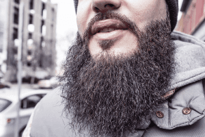 A close up of a long black beard in an urban environment