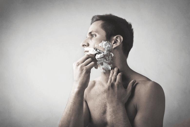 Man Shaving cheek using razor and shaving cream