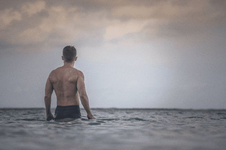 Man with a shaved back in sea looking at the sky