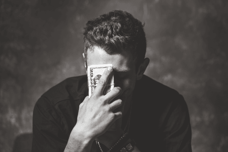Man holding banknotes against forehead