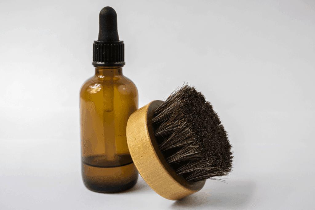 Beard brush leaning on beard oil bottle on white background
