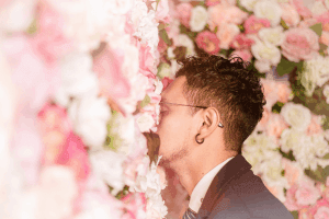 Man in suit smelling pink flower wall