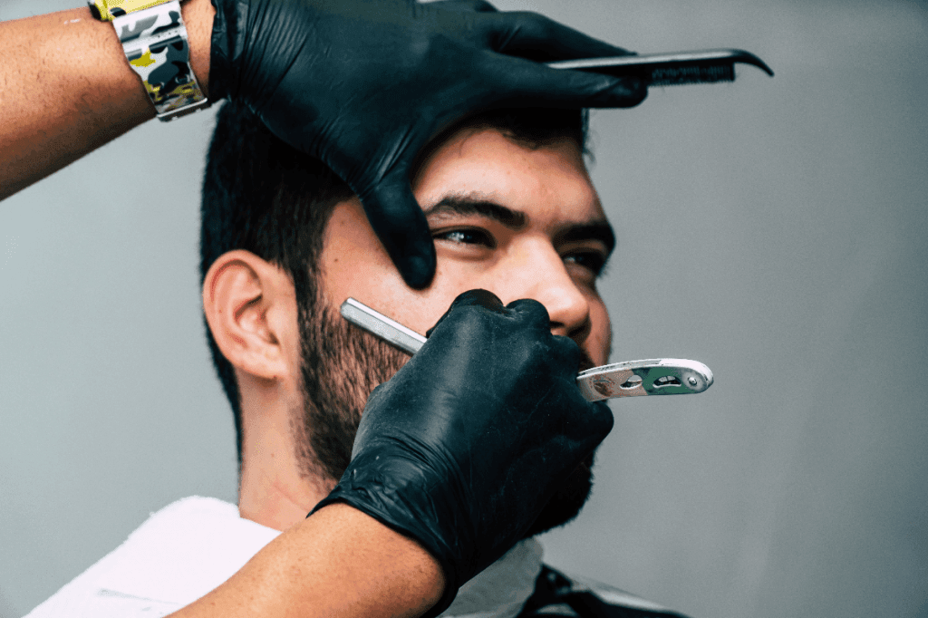 Man getting a shave using a straight razor on his cheek