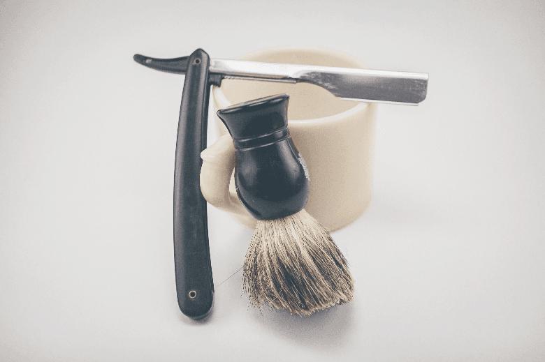 Straight razor and shaving brush leaning on shaving mug in white space