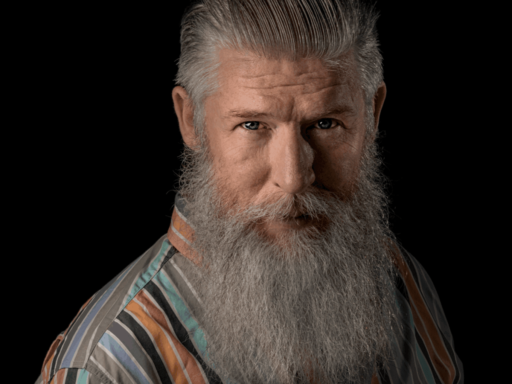 Man with gray long beard, sweapt back hair and colorful shirt