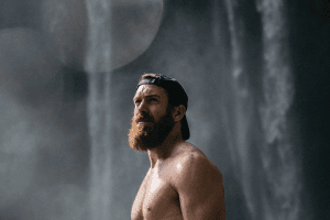 Naked man standing besides a waterfall with a baseball cap