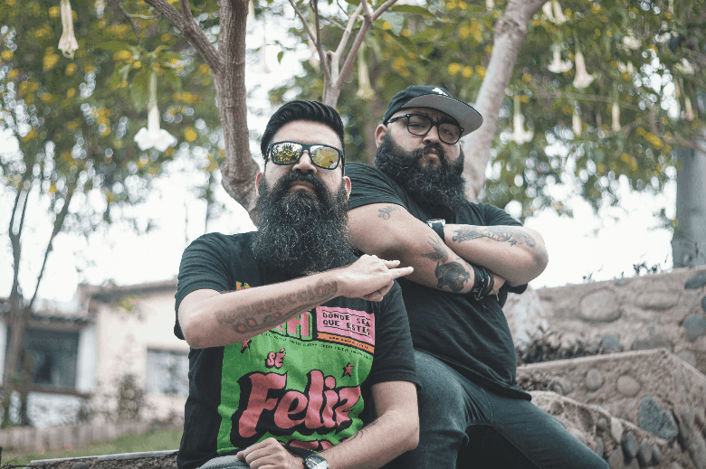 Two tattooed men sitting down in nature