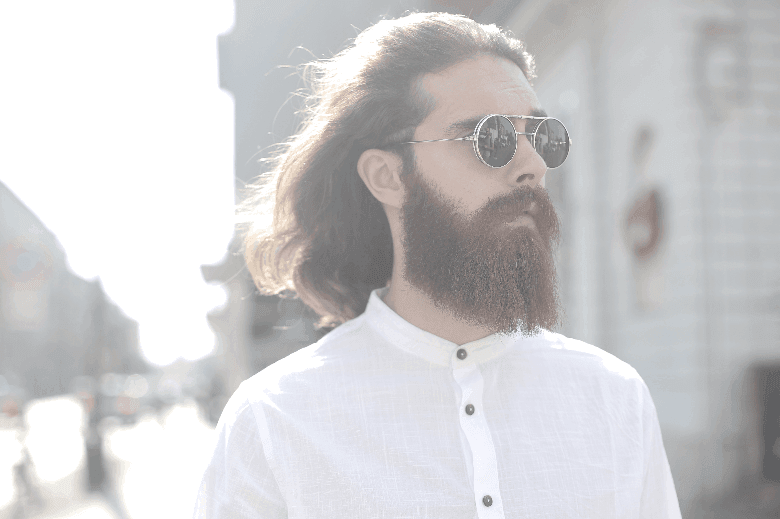 man in white shirt and with lon beard looking to the side in an urban setting