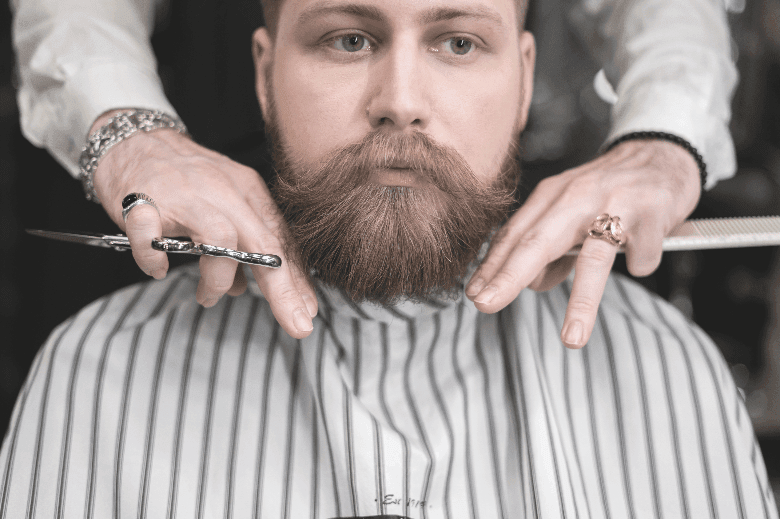 Man in barbers chair receiving a beard trim