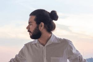 A man in white shirt and long hair in a bun style