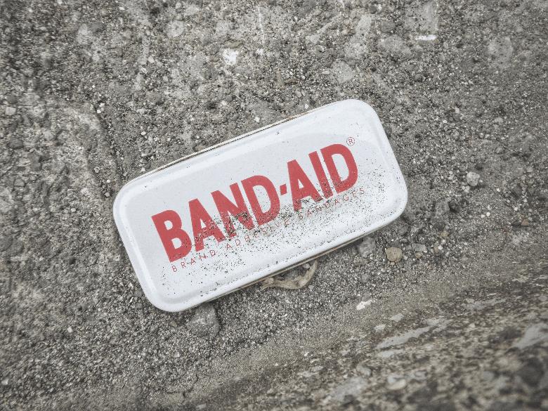 metal band-aid box on dirt