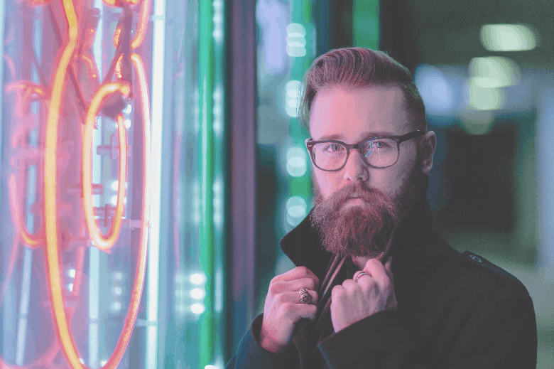 Man with beard glasses on the street by neon lights