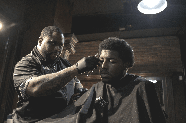 Man with afro getting haircut on the side