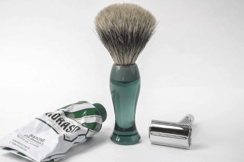 Double edge razor next to a shaving brush and shaving cream