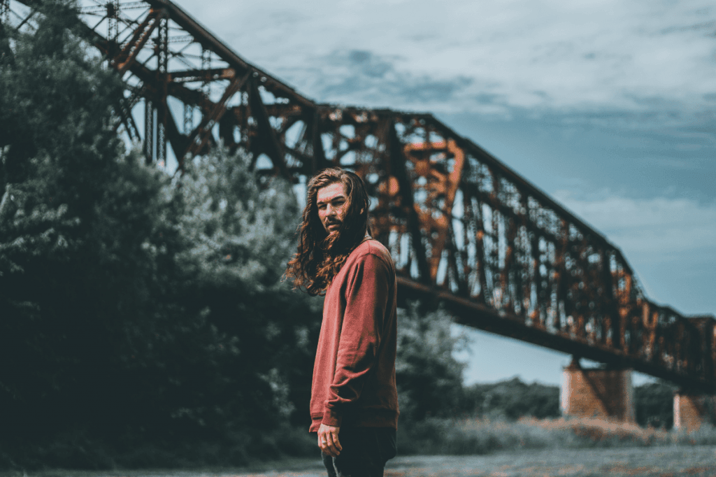 Man in red swetshirt and with long hair standing in front of a bridge