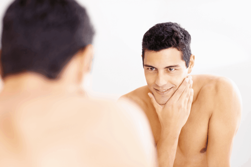 Man looking in a mirror touching his chin